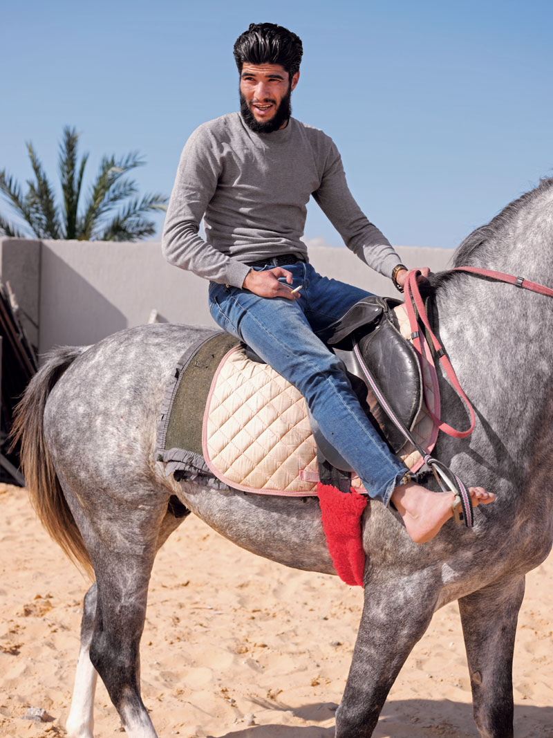 LIBYA. Zawiyah. April 5, 2017. Abdulrahman Al-Bija, a former revolutionary fighter and now a Libyan Coast Guard commander in Zawiyah, rides his horse in a farm on the outskirts of Zawiyah.